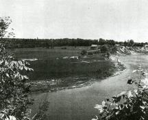 "1960 photograph of Donaldson during the course of the excavations by James V. Wright. The photographer is looking east from the opposite bank of the river.; J.V. Wright and J.E. Anderson, ""The Donaldson Site,"" National Museum of Canada Bulletin 184, (1963))"