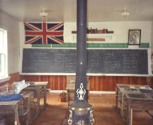 Showing central stove, desks, flag, etc.; Friends of Lucy Maud Montgomery School, Lower Bedeque, 2004