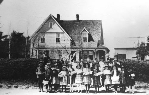 House with group of children, c. 1910