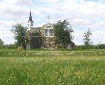 View northwest at fieldstone shrine (note iron cross on top of the grotto, replica; Government of Saskatchewan, Marvin Thomas, 2004.
