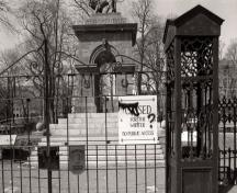 Alternate view of the Sebastopol memorial through the main entrance gate to the Old Burying Ground, 1993.; Agence Parcs Canada / Parks Canada Agency, 1993.