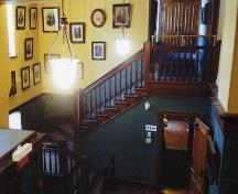 Entrance hall and stairs with pendant lighting.; Source: Andrew Waldron, Parks Canada, 2014.