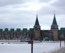 The symmetrically organized entry facade with central arched doorway flanked by pinnacled circular towers facing the parade square.; Source: Andrew Waldron, Parks canada, 2014.