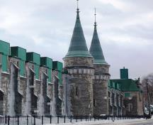 View of buttresses creating a regular definition of bays, faux gun embrasures on the ground level and elaborate French Renaissance-style windows breaking the eave line at the second storey.; Source: Andrew Waldron, Parks Canada, 2014.