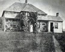 Front elevation with woman and child out front ca. 1900, MacRae-Bitterman House, Middle River, Cape Breton, NS.; Courtesy of the Beaton Institute, Cape Breton University.