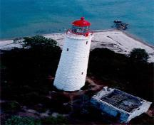 Aerial view of the Chantry Island Lighthouse showing its tall, round, slightly tapered form corbelled at the top to form a gallery and base for the lantern, 1990.; Canadian Coast Guard / Garde côtière canadienne, 1990.