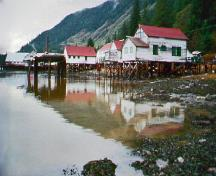 General view of the North Pacific Cannery, showing the wooden pilings that support the buildings over the water, 2002.; Parks Canada Agency / Agence Parcs Canada, 2002.