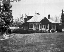 General view of the the Superintendent's Residence and Works Garage showing the modest massing of the T-shaped building.; Parks Canada Agency / Agence Parcs Canada, n.d.