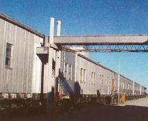 General view of Module Train B, showing its exterior metal cladding and the size, form and spacing of door and window openings dictated by each modules function, 1998.; Canada, North Warning System Office / Bureau du système d'alerte du Nord, 1998.