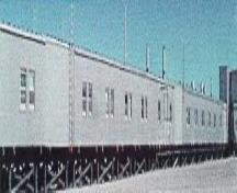 Side façade of Module Train A, showing its exterior metal cladding and the size, form and spacing of door and window openings dictated by each modules function, 1998.; (Canada, North Warning System Office / Bureau du système d'alerte du Nord , 1998.)