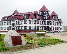 General view of the former Lunenburg Academy, showing the mansard roof in the French Empire style with segmental dormer windows, massive central chimney, and the three projecting towers with pyramidal roofs.; Parks Canada Agency / Agence Parcs Canada.