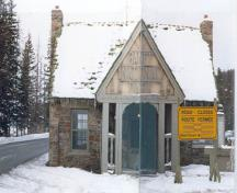 "Façade of Building 2, showing the front porch, the gable end of which frames the words ""Banff National Park"", which protects the main entrance, 1985.; Parks Canada Agency / Agence Parcs Canada, 1985."