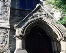 View of an entrance of St. George's Anglican Church, showing the rusticated stone exterior, 1995.; Parks Canada Agency / Agence Parcs Canada, P. St. Jacques, 1995.
