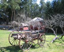 1589 Millstream Road, Caleb Pike Heritage Park, view from Millstream Road to Old Schoolhouse showing wagon and fruit trees; Ditrict of Highlands, 2000