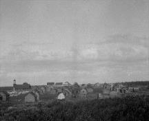 Historic photograph of Fort McPherson showing dwellings and the Anglican Church on the left of the image, standing still, ca. 1930; Indian and Northern Affairs Canada, Library and Archives Canada | Affaires indiennes et du Nord Canada, Biliothèque et Archives Canada, PA-102490.