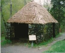 Front elevation of the Lone Shieling, showing its simple, low massing composed of a rectangular structure with low, heavy walls and a steeply pitched hipped roof, 1993.; Parks Canada Agency / Agence Parcs Canada, 1993.
