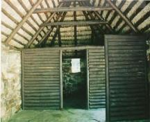 Interior view of the Lone Shieling, showing the simple interior rectangular plan divided into two sections by log partitions, 1993.; Parks Canada Agency / Agence Parcs Canada, 1993.