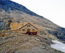 General view of Abbot Pass Refuge Cabin, showing its picturesque siting in a barren and remote mountain pass.; Parks Canada Agency / Agence Parcs Canada.