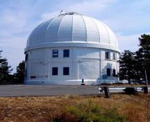 General view of the Dominion Astrophysical Observatory showing its simple cylindrical massing with dome.; Parks Canada / Agence Parcs Canada, Andrew Waldron.