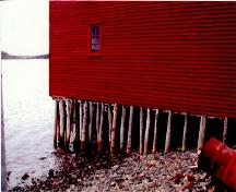 Exterior photo of Grant's Stage, Trinity, Trinity Bay, NL.  Photo showing wooden support posts as building extends over the water.; HFNL 2005