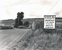 "The sign in this c1940 photo reads, ""MAGNETIC HILL:  TO APPRECIATE THIS PHENOMENON PROCEED TO SPOT INDICATED BY WHITE POST TURN OFF MOTOR RELEASE BRAKES""; Moncton Museum"