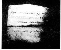 "Historic photo of the headstone of the first settler of Cow Head, Mary Payne.  Inscription reads,""In memory of Mary Payne who died ... age 69 years"".; HFNL 2005."