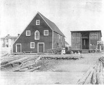 "The Mockbeggar Plantation c1920s.  The large building in the center of the photo is referred to as the ""fish store"".  To the right of that is the barter shop and to the left is the Bradley residence.  ; Department of Tourism, Culture and Recreation 2005"